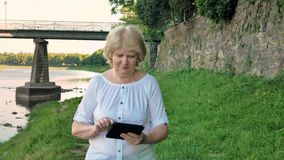 Elderly woman walks along the waterfront using tablet computer. Bridge and vintage wall of wild stone in the background stock video