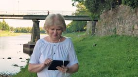Elderly woman walks along the waterfront and using tablet computer with earphones. Bridge and vintage wall of wild stone in the ba. Ckground stock video