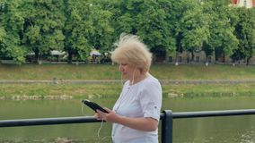 Elderly woman walks along the waterfront and using tablet computer with earphones. River in the background stock footage