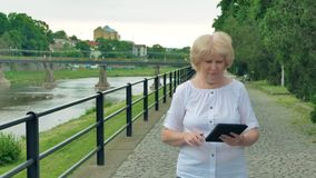 Elderly woman walks along the waterfront and using tablet computer. River in the background. Elderly woman walks along the waterfront and using tablet computer stock footage