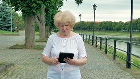 Elderly woman walks along the waterfront and using tablet computer. River in the background. Elderly woman walks along the waterfront and using tablet computer stock video footage
