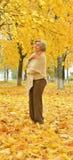 Elderly woman walks in autumn park Stock Image