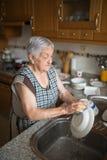 Elderly woman washing dishes Stock Images