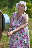 Elderly woman washing hands in washstand outdoor Royalty Free Stock Photo