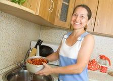 Elderly woman washing strawberries. In the kitchen sink Stock Photo