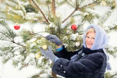 Elderly woman putting ornaments on Christmas tree outdoors. Elderly woman wearing fur coat putting ornaments on Christmas tree outdoors, snowy day royalty free stock image