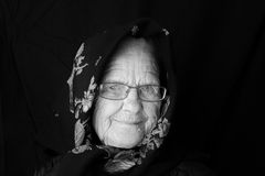 Elderly woman wearing a scarf. Elderly woman with eyeglasses and wrinkles wearing a scarf Royalty Free Stock Photography
