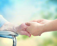 Elderly woman in wheel chair holding hands with young caretaker royalty free stock photography