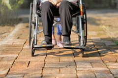 Elderly woman in wheelchair with caregiver royalty free stock photos