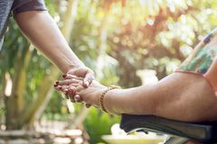 Elderly woman in wheelchair holding hands with young woman outsi Stock Images