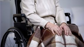 Elderly woman in wheelchair massaging painful knee joints, health problems royalty free stock photography