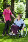 Elderly woman in a wheelchair with a nurse Stock Images