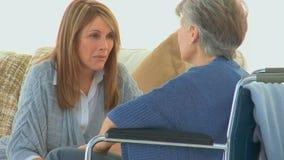 Elderly woman in a wheelchair speaking to her friend