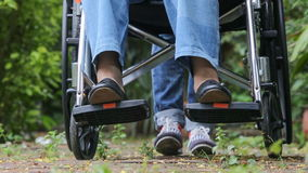 Elderly woman in wheelchair walking with caregiver stock video