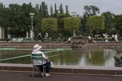 Elderly woman in a white blouse and hat sitting on a chair admiring the view of the pool stock photos