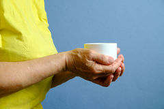 Elderly woman with white cup of tea Royalty Free Stock Photos