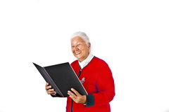 Elderly woman with white hair reading in a book and making a Royalty Free Stock Photo