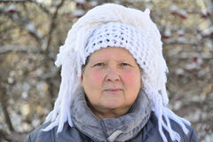 Elderly woman in  white knitted shawl on her head Royalty Free Stock Photo