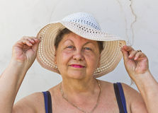 An elderly woman in a white wide-brimmed summer hat Stock Photo