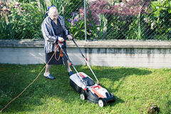 Elderly woman who cuts the grass in the garden Stock Photo