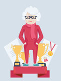 Elderly woman on a winners podium. Elderly grey-haired woman in glasses on a winners podium surrounded by two gold trophies and certificates having achieved a Royalty Free Stock Photos
