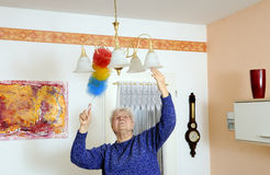 Elderly woman wiped dust Royalty Free Stock Photo