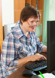 Elderly woman working with computer Stock Image