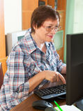 Elderly woman working with computer Royalty Free Stock Photos