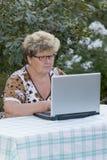 Elderly woman working on  computer in the garden Stock Photo