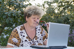 Elderly woman working on  computer in the garden Stock Image
