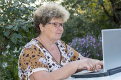 Elderly woman working on  computer in the garden Stock Photography