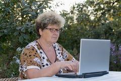Elderly woman working on  computer in the garden Stock Photos