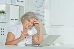 Elderly woman working on laptop Stock Image