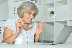 Elderly woman working on laptop Royalty Free Stock Photos