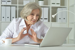 Elderly woman working on laptop Stock Photography