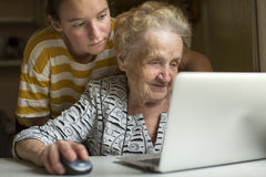 Elderly woman working on laptop with the help of his granddaughter. Education. Royalty Free Stock Photo