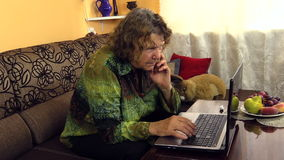 Elderly woman working with laptop notebook computer at home stock video footage