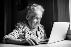 Elderly woman works on a laptop. Working. Royalty Free Stock Photos