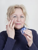 Elderly woman with Wrinkle Cream Royalty Free Stock Image