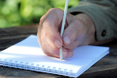 Elderly woman writes a letter. The hand of an elderly woman with a pen and a sheet of white paper on the wooden table Stock Photography