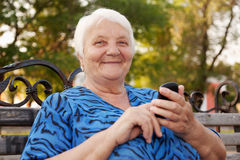 Senior Woman and new technologies. The elderly woman, writes the message in phone Royalty Free Stock Images