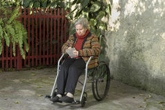 Elderly Woman Writing in Wheelchair - Horizontal Stock Photo