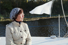 Elderly woman yachtsman looks afar on a sailing yacht. At sunny day Stock Photography