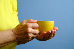 Elderly woman with yellow cup of tea Stock Photo