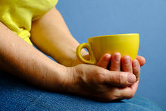 Elderly woman with yellow cup of tea Royalty Free Stock Photos
