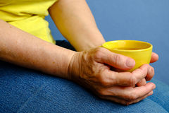 Elderly woman with yellow cup of tea Stock Photography
