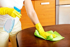 Elderly woman in yellow gloves cleaning table Stock Photo