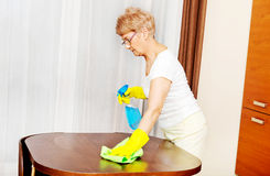 Elderly woman in yellow gloves cleaning table Royalty Free Stock Image