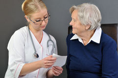Elderly woman and a young doctor. Stock Photos