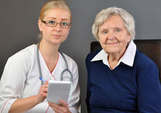Elderly woman and a young doctor. Stock Images